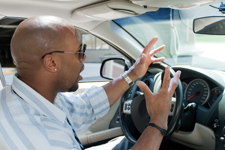 expressing: An irritated business man driving a car is expressing his road rage with his hands in the air. Stock Photo