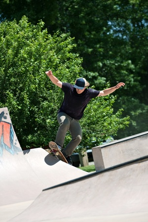 Action shot of a skateboarder going up a concrete skateboarding ramp at the skate park. Shallow depth of field. photo