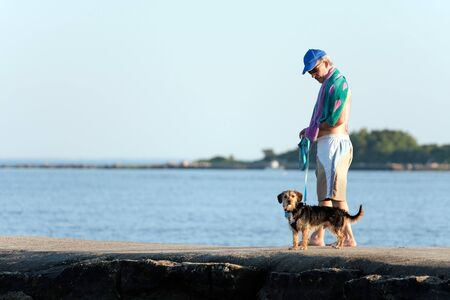 A middle aged man walks a cute borkie beagle yorkie mix puppy at the beach. photo