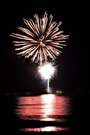 Beautiful fireworks going off over the dark night sky reflecting over the water. photo