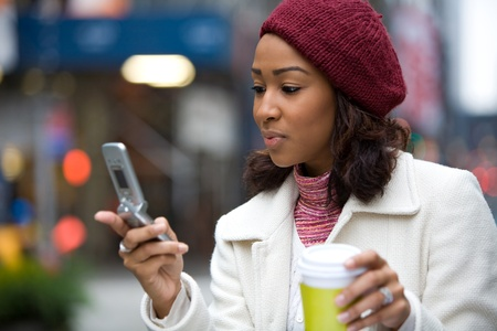 An attractive African American business woman checks her cell phone in the city.  She could be text messaging or even browsing the web via 4G connection.
