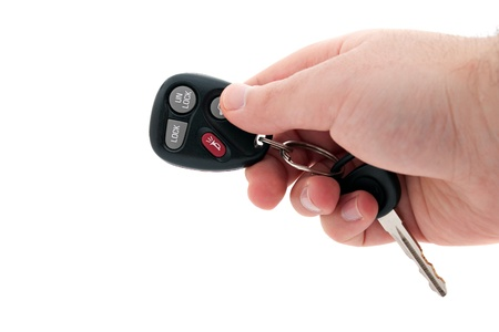 A hand holding car keys and a remote control for keyless entry isolated over white. Archivio Fotografico