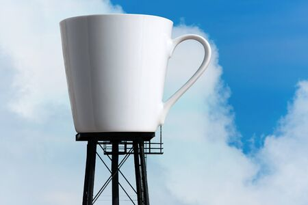 enormous: An enormous supply of coffee in the form of a coffee mug atop water tower stilts.  A funny concept for caffeine addiction or coffee lovers.
