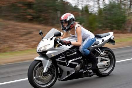 A woman drives a motorcycle at highway speeds with motion blur visible in the background.