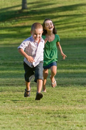 A young brother and sister running through a green grassy field with smiles on their faces.