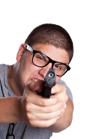 An angry looking teenager wearing black frame glasses points a black handgun at the viewer. Shallow depth of field with focus on the face. photo
