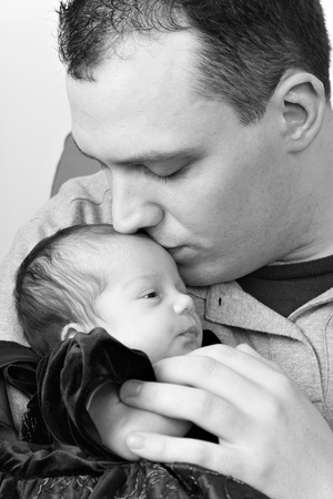 A newborn baby girl being by her dad as he kisses her head in black and white. photo