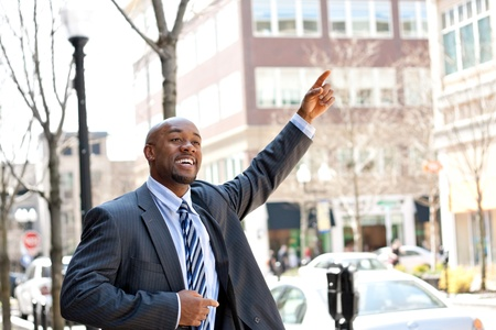 busy street: An African American business man raises his hand to hail a cab in the city.