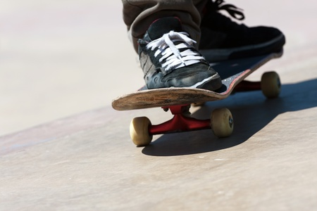 Close up of a skateboarders feet while skating on concrete.  Shallow depth of field. Stock Photo