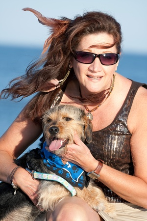 beagle mix: A middle aged woman by the ocean holding a cute mixed breed Beagle Yorkshire terrier dog also referred to as a Borkie. Stock Photo