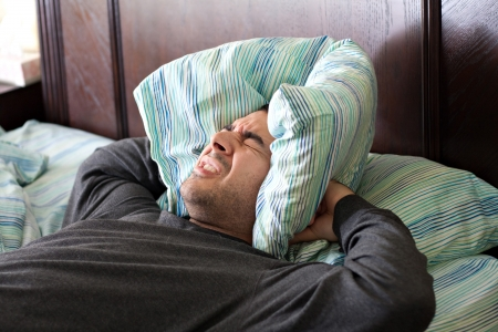 A man having trouble sleeping squeezes a pillow around his ears for some peace and quiet. photo