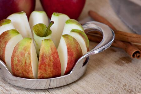 wedges: An apple is sliced into wedges and cored using a handy kitchen tool.