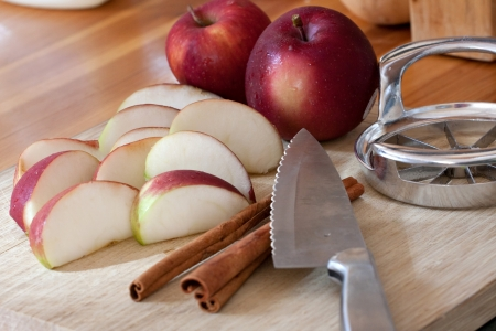 An apple is sliced up into wedges on a cutting board. This is the start of preparation to making a homemade apple pie. photo