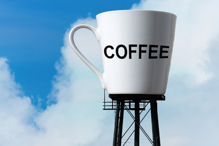 large size: Conceptual image of a large supply of coffee in the form of a coffee mug atop water tower stilts.  A funny concept for caffeine addiction or coffee lovers.