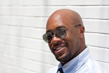bald: An African American business man wearing his sunglasses in the city.