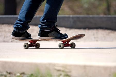schaatsen: Close up van een skateboarders voeten, terwijl schaatsen op beton bij het skatepark.