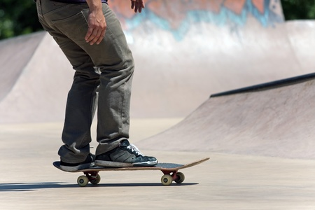 Action shot of a skateboarder skating at the skate park with concrete ramps. Stock Photo