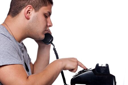 dialing: Young man dials a vintage rotary phone isolated over a white background. Stock Photo