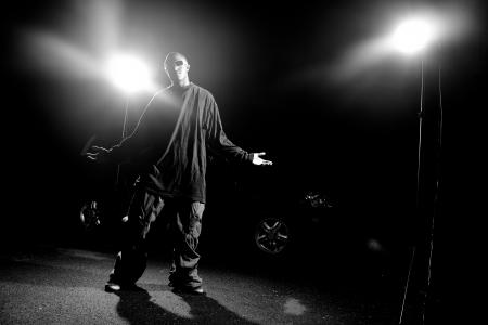 Afro-américaine jeune homme portant des vêtements amples qui pose sous un éclairage dramatique avec lens flare.