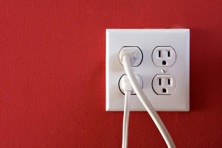 socket: Electrical outlets with four spaces and two of them have chords plugged in. Stock Photo