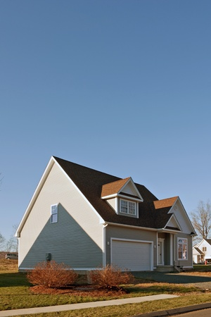 house siding: Modern custom built house newly constructed with a 2 car garage in a residential neighborhood.   Stock Photo