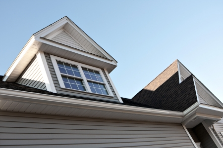 roof shingles: Close up view of a newly built house rooftop soffit and dormers.