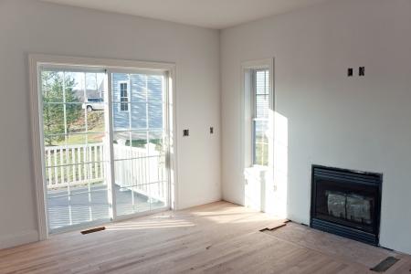 현관: 벽에있는 작은 파우치 미완성 가스 벽난로 로그 삽입으로 이어지는 유리 미닫이 문 현대 홈 인테리어입니다.
