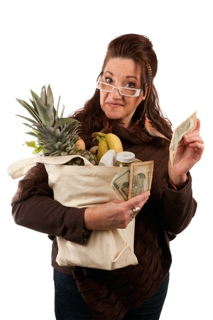 Middle aged female shopper smiling with a handful of cash acting proud of how much money she has saved on her grocery shopping bill.