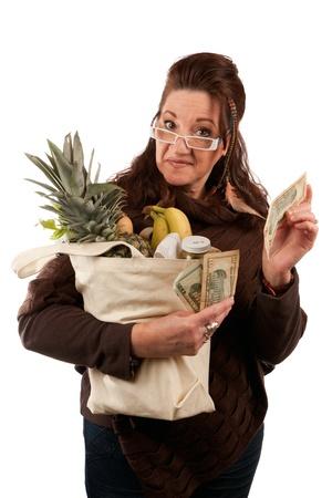 Middelbare leeftijd vrouwelijke shopper lachend met een handvol geld handelen trots op hoeveel geld ze op haar boodschappen wetsvoorstel heeft gered.