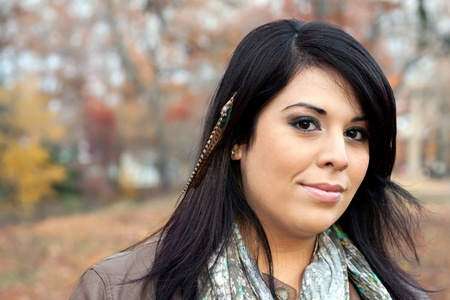 hair feathers: Beautiful young Hispanic woman wearing custom feather hair extensions in her black hair.