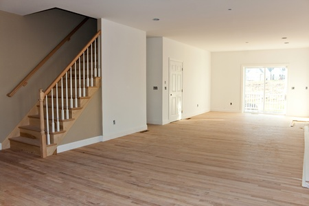 New home construction inter room with unfinished wood floors stairway and railings. Electrical and hvac connections also are partially unfinished. Stock Photo - 12442903
