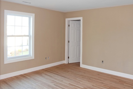 Newly constructed house interior room with unfinished wood floors window and closet door.  Electrical connections are partially unfinished. Stock Photo
