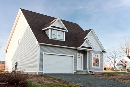 house siding: Modern custom built house newly constructed with a two car garage in a residential neighborhood.