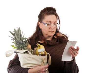 spent: Middle aged woman carefully examining her register receipt reviewing her grocery shopping bill.