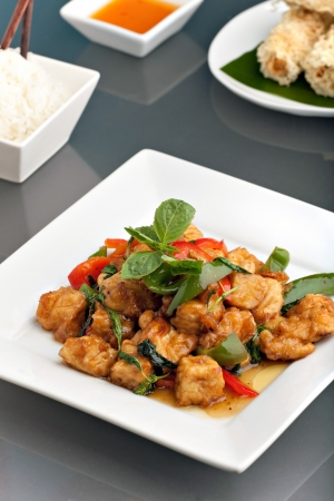 Fresh Thai food stir fry with stir fried tofu jasmine rice and crispy taro root crusted Thai spring rolls appetizer. Stock Photo