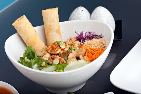 Freshly prepared Thai salad with spring rolls in a bowl with some chopsticks.