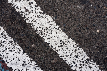 single lane road: Close up of the twin white lines painted on the street asphalt.