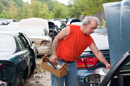 junk yard: A man browses for car parts on decommissioned used cars at an automotive junk yard. Stock Photo