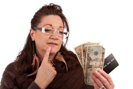 lucrative: Middle aged woman carefully trying to decide between using old fashioned cash or a plastic credit card. Stock Photo
