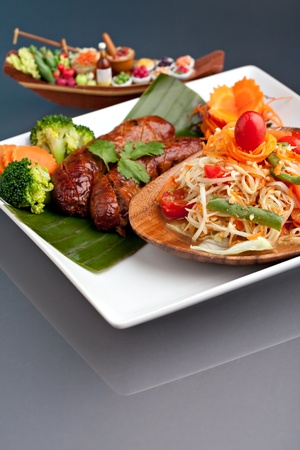 Plate of freshly prepared Thai sausage and som tum green papaya salad. photo