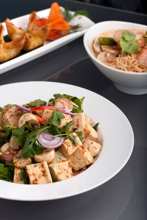 Fresh Thai food stir fry with tofu shrimp noodle soup and other appetizers. photo