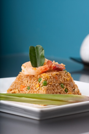 Thai style shrimp fried rice presented on a square white plate in the shape of a pyramid. 版權商用圖片