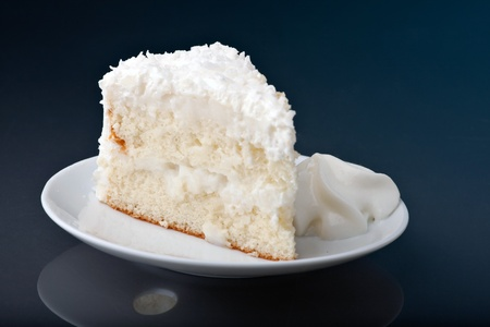 A fresh piece of coconut cream cake on a white plate with a bit of whipped cream on the side. photo