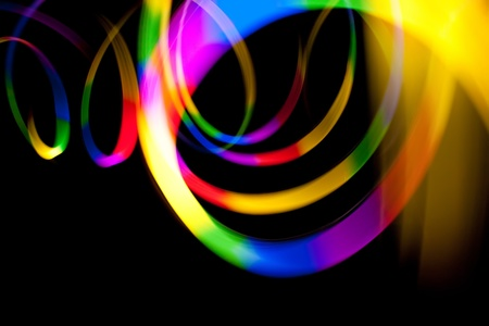 light trails: Abstract rainbow colored light streaks isolated over a dark black background. Stock Photo