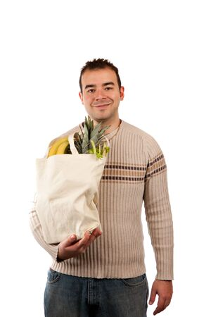 White male grocery shopper smiling while holding a canvas bag full of fresh food items. photo