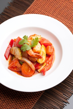 plating: Thai style sweet and sour shrimp dish presented beautifully on a round white plate.