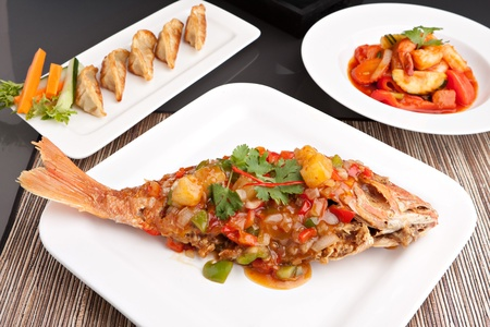 Freshly prepared Thai style whole fish red snapper dinner with sweet and sour shrimp and pan fried gyoza dumplings appetizer.   photo
