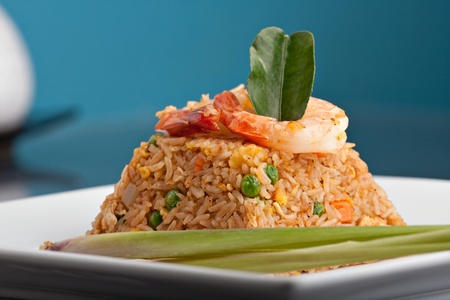 A Thai dish of shrimp fried rice presented on a square white plate in the shape of a pyramid.