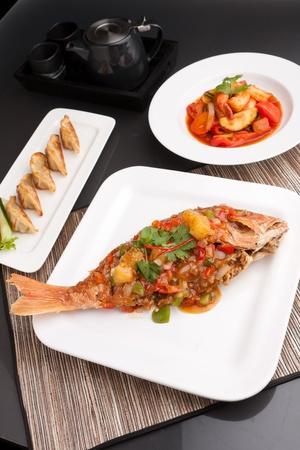 Recién preparada al estilo tailandés toda cena de pescado pargo rojo con camarones agridulce y pan frito aperitivo gyoza bolas de masa hervida. Foto de archivo - 13104680