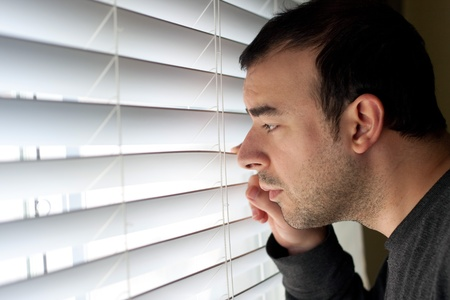 molesto: Asustado o molestado hombre se asoma por la ventana a través de las persianas.